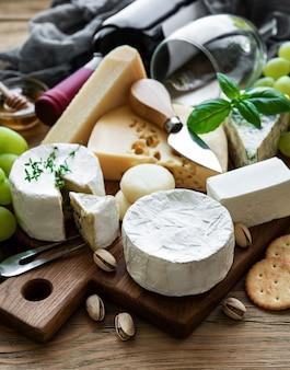 Verschiedene käsesorten, trauben und wein auf einem holztisch