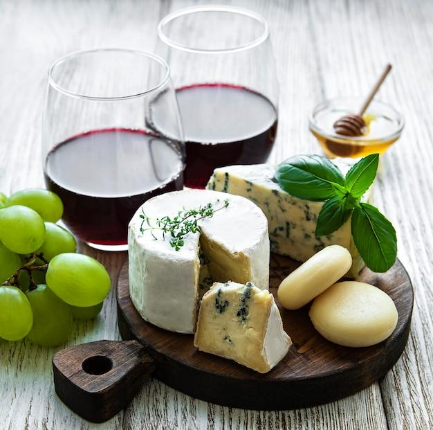 Verschiedene käsesorten, trauben und wein