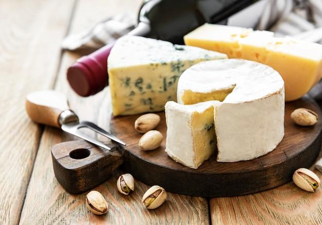 Verschiedene käsesorten, trauben, wein und snacks auf einem alten holztisch