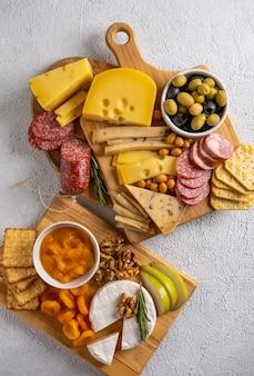 Verschiedene käsesorten und aufschnitt. draufsicht auf einem weißen hintergrund. verschiedene käsesorten mit nüssen, cracker, oliven, salami und rosmarin.