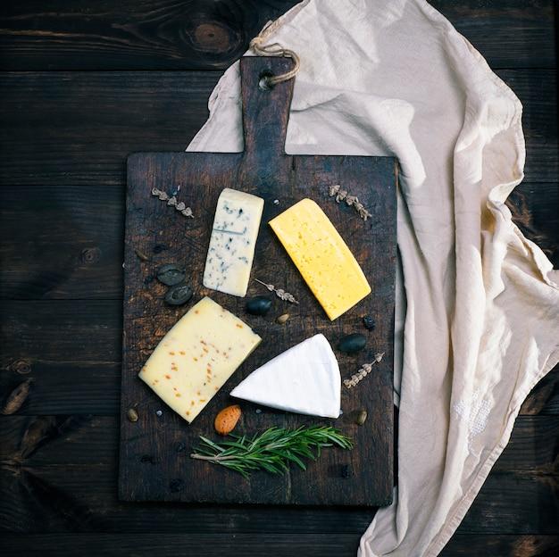 Verschiedene käsestücke auf einem braunen holzbrett: