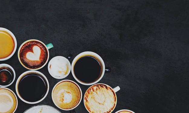 Verschiedene kaffeetassen auf schwarzer oberfläche