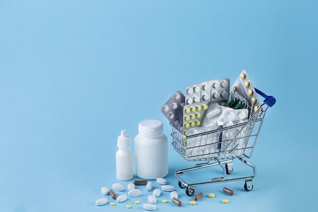 Verschiedene kapseln, tabletten und medikamente im einkaufswagen und pillen, die aus weißer flasche auf blauem hintergrund verschüttet werden. medizinkonzept kaufen und einkaufen.