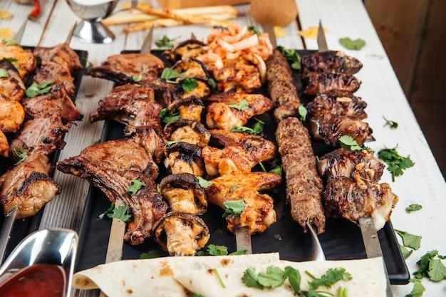 Verschiedene kaukasische spieße shashlyq mit fleisch und gemüse