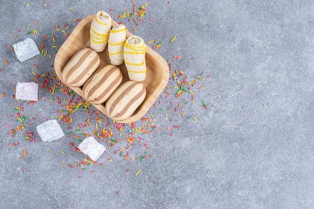 Verschiedene kekse auf holzteller mit bonbons und streuseln