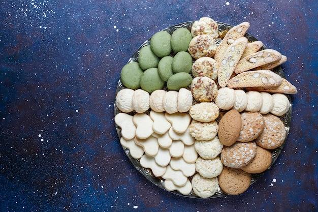 Verschiedene kekse in einem holztablett auf grauem hintergrund