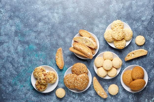 Verschiedene kekse in einem holztablett auf grauer wand