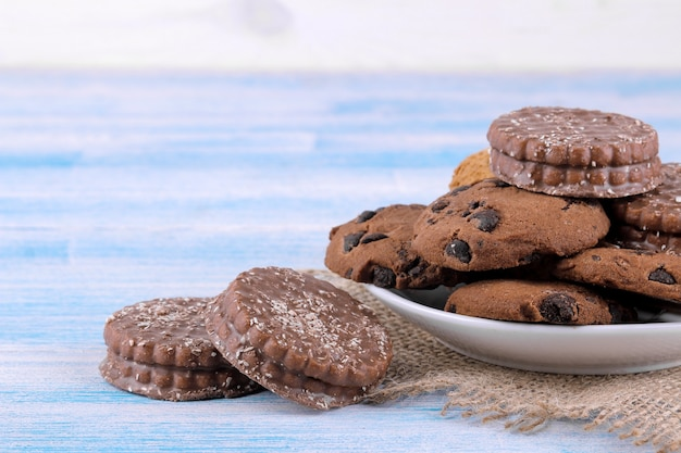 Verschiedene kekse in einem teller auf einem blauen tisch mit einer serviette. backen. lecker. platz für text.