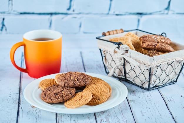 Verschiedene kekse in teller und korb und eine tasse auf blauem tisch.