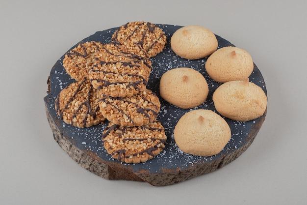 Verschiedene kekse stapelten sich auf einem holzbrett auf marmorhintergrund.