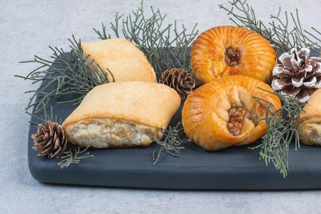 Verschiedene kekse, tannenzapfen und tannenzweig auf einem holztablett, auf dem marmor.