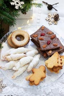 Verschiedene kekse, tannenzweige und eine girlande auf hellem hintergrund. rustikaler stil, selektiver fokus.