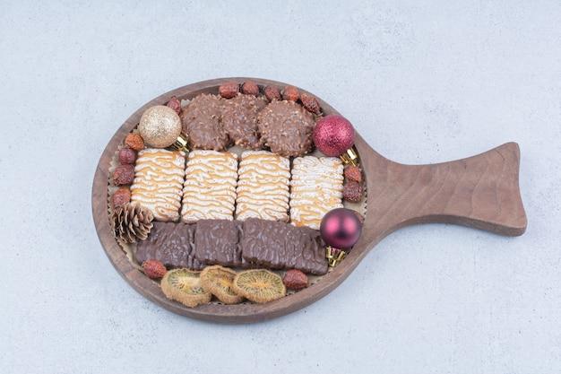 Verschiedene kekse, trockenfrüchte und weihnachtskugeln auf holzbrett.