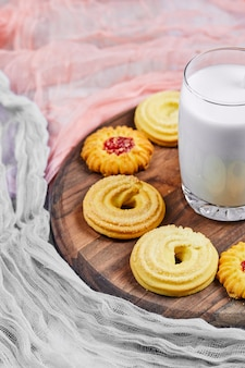 Verschiedene kekse und ein glas milch auf einem holzteller.