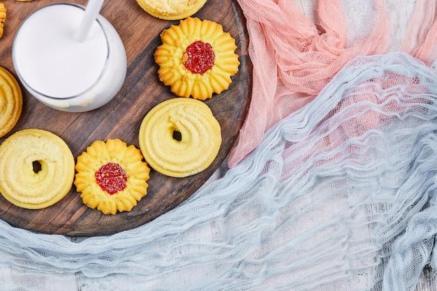 Verschiedene kekse und ein glas milch auf holzteller mit tischdecken.