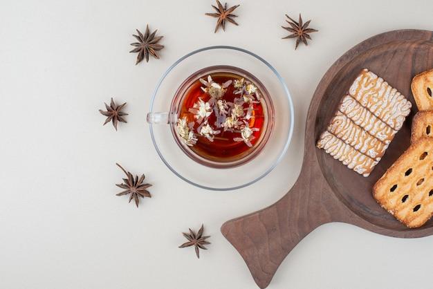 Verschiedene kekse und eine tasse tee auf weißem grund