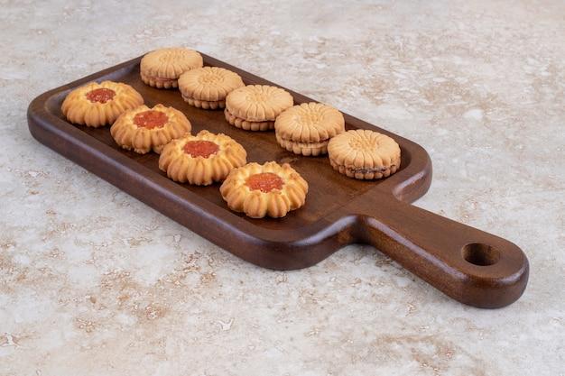 Verschiedene kekse und geschälte erdnüsse auf einem brett, auf dem marmor.