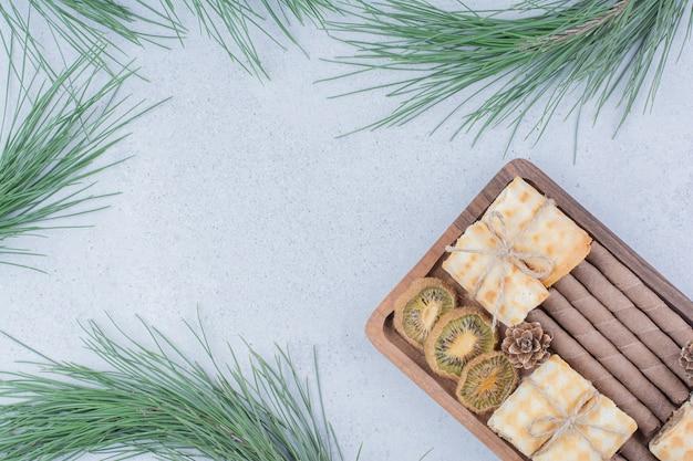 Verschiedene kekse und getrocknete kiwischeiben auf holzbrett.