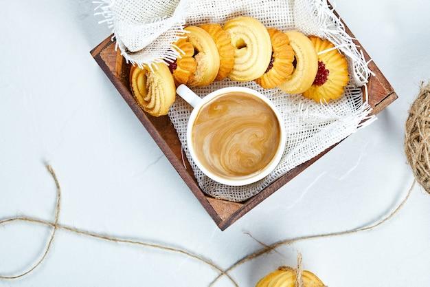 Verschiedene kekse und kaffee auf weißem hintergrund. hochwertiges foto