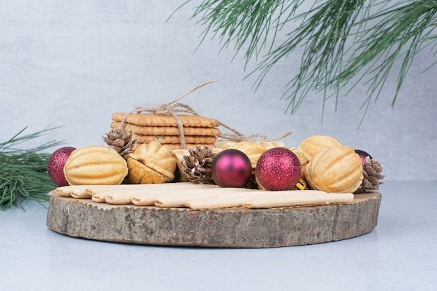 Verschiedene kekse und weihnachtsschmuck auf holzbrett.