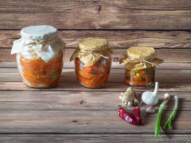 Verschiedene kimchi in gläsern auf einem braunen holztisch.