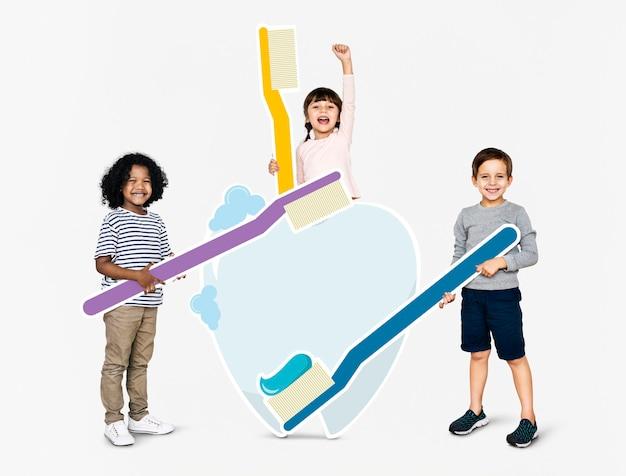Verschiedene kinder mit zahnpflegesymbolen