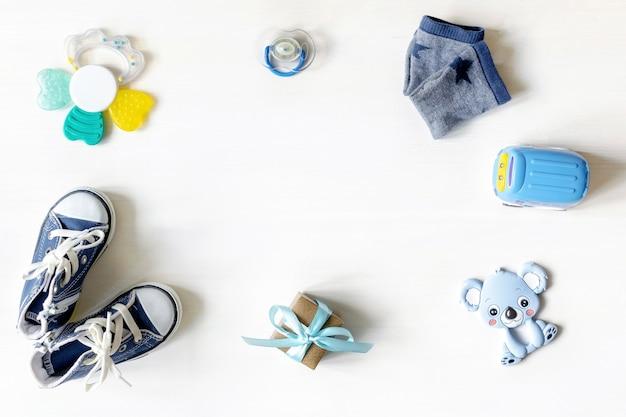 Verschiedene kinderspielzeuge, auto, geschenkbox auf weißem tisch mit kopierraum, flache lage. babyparty, accessoires, dekorationen, sachen, geschenk für den ersten geburtstag des jungen mädchens, neugeborenenparty