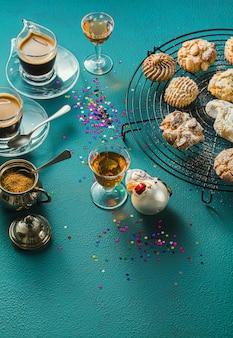Verschiedene klassische italienische hausgemachte mandelkekse mit espressokaffee und gläsern süßem schnaps auf dem tisch, weihnachtsdekoration