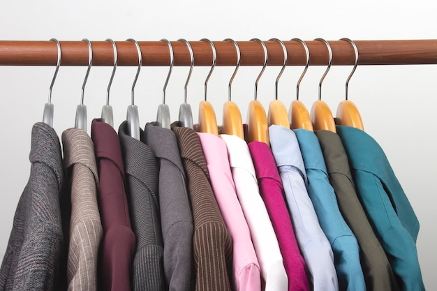 Verschiedene klassische jacken und hemden für frauenbüros hängen an einem kleiderbügel, um kleidung aufzubewahren