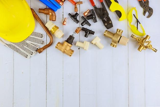 Verschiedene klempnerwerkzeuge, rohrverbindungsstücke an einem heimwerker-installationsmaterial, einschließlich kupferrohr, winkelverbindung, schraubenschlüssel und schraubenschlüssel.