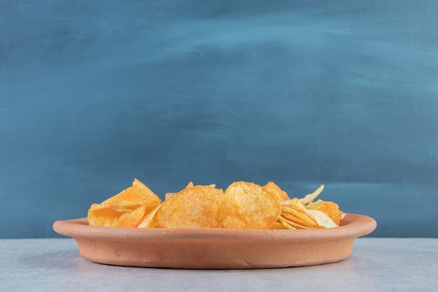 Verschiedene knusprige chips auf einem teller auf stein gelegt.