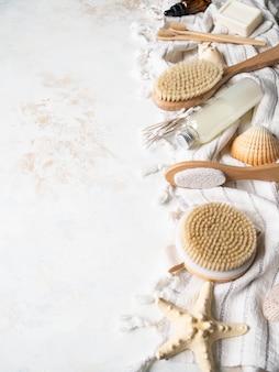 Verschiedene körperbürsten, bimsstein, kosmetik, bambuszahnbürste, kosmetik auf weißem baumwolltuch. kopieren sie platz. plastikfreies leben. null-abfall-konzept. kopieren sie platz