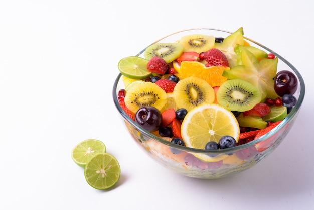Verschiedene köstliche früchte serviert auf glasschale isoliert