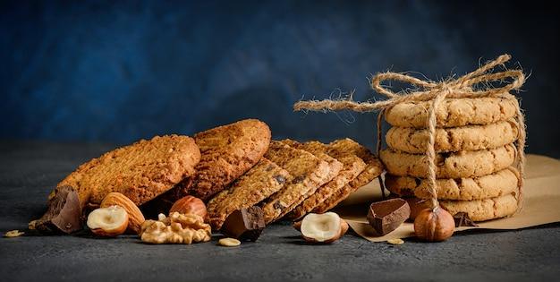 Verschiedene köstliche schokoladenchips und nussplätzchen auf dunkelblauem hintergrund.