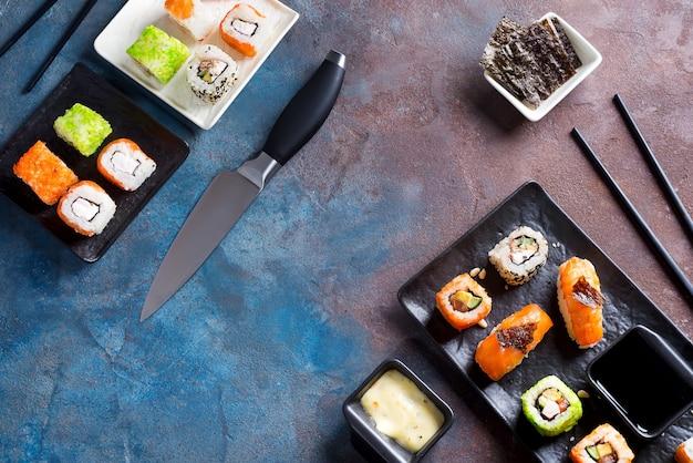 Verschiedene köstliche sushi und rollen stellten auf schiefer, soße auf dunklem steinhintergrund ein