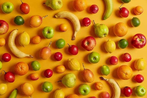 Verschiedene köstliche tropische früchte auf gelbem hintergrund. bananen, äpfel, zitronen, cumquat, limetten, birnen zum essen. superfood und gesunde ernährung konzept. sommer und ernte. sicht von oben