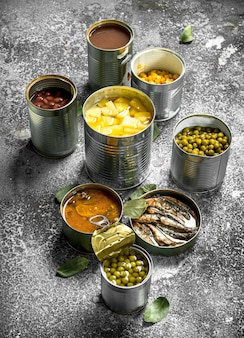Verschiedene konserven mit fleisch, fisch, gemüse und obst in blechdosen auf rustikalem tisch.