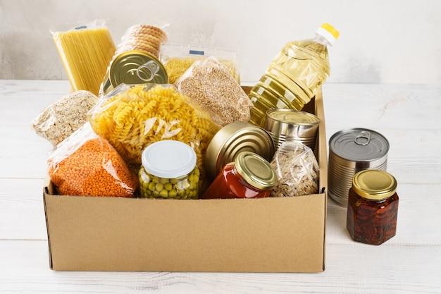 Verschiedene konserven, nudeln und müsli in einem karton. lebensmittelspenden oder lebensmittelversorgungskonzept.