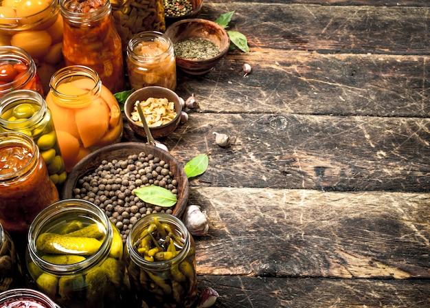 Verschiedene konservierte gemüse aus gemüse und pilzen in gläsern. auf einem holztisch.