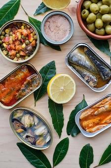 Verschiedene konservierte gemüse und fisch, zitrone und oliven. auf holzsockel.