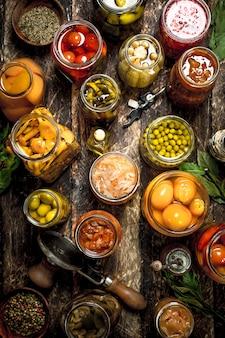 Verschiedene konservierte gemüse und pilze mit seemann und gewürzen. auf einem holztisch.