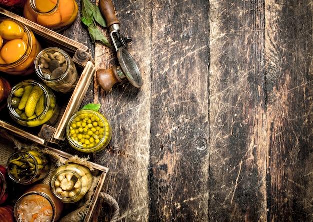 Verschiedene konservierte gemüse und pilze mit seemann und gewürzen auf holztisch.