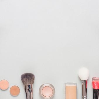 Verschiedene kosmetische produkte mit bürsten an der unterseite des weißen hintergrundes