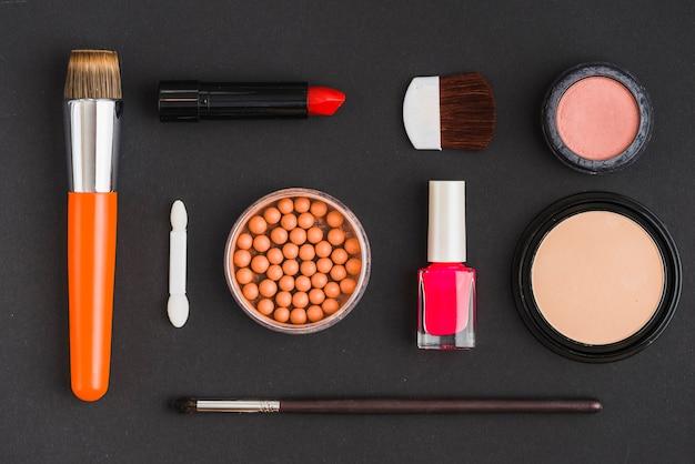 Verschiedene kosmetische produkte und make-up pinsel auf schwarzem hintergrund