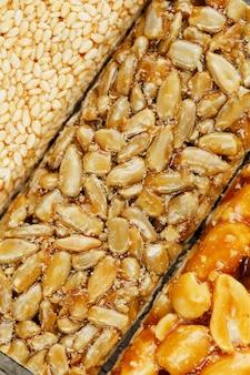 Verschiedene kozinaki, bonbons aus sonnenblumenkernen, sesam und erdnüssen, gefüllt mit brillanter glasur. makro