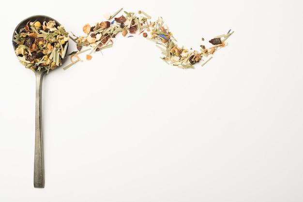 Verschiedene kräuter für die herstellung von gesundem tee im schöpflöffel auf weißem hintergrund