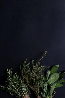 Verschiedene kräuter im schwarzen tisch, draufsicht