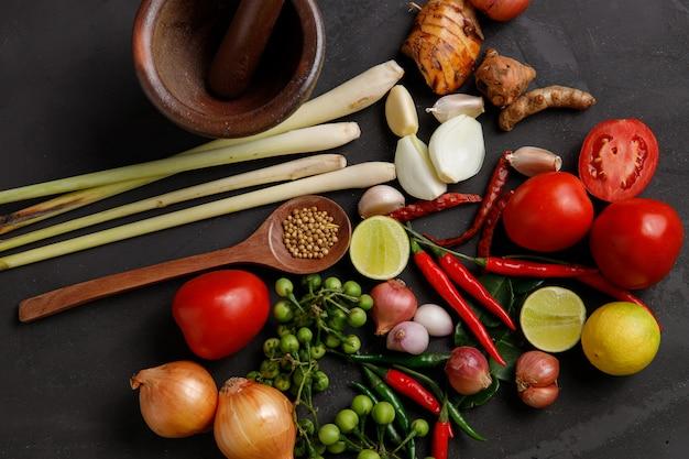 Verschiedene kräuter und zutaten zum kochen auf dunklem hintergrund.