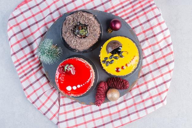 Verschiedene kuchen auf dunklem brett mit weihnachtsschmuck.
