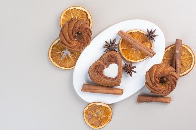 Verschiedene kuchen mit orangenscheiben, nelken und zimt auf weißem teller